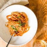 bowl of pasta with fork on wood table top