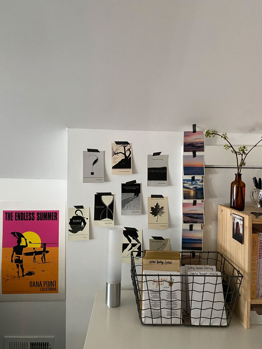 postcards and photos and poster on wall above desk with wire basket