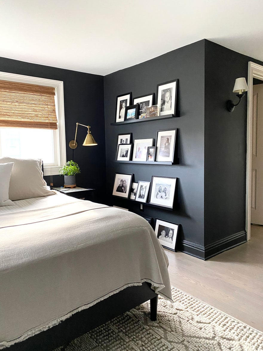 corner of bed in black room with brass sconce and photos on ledges