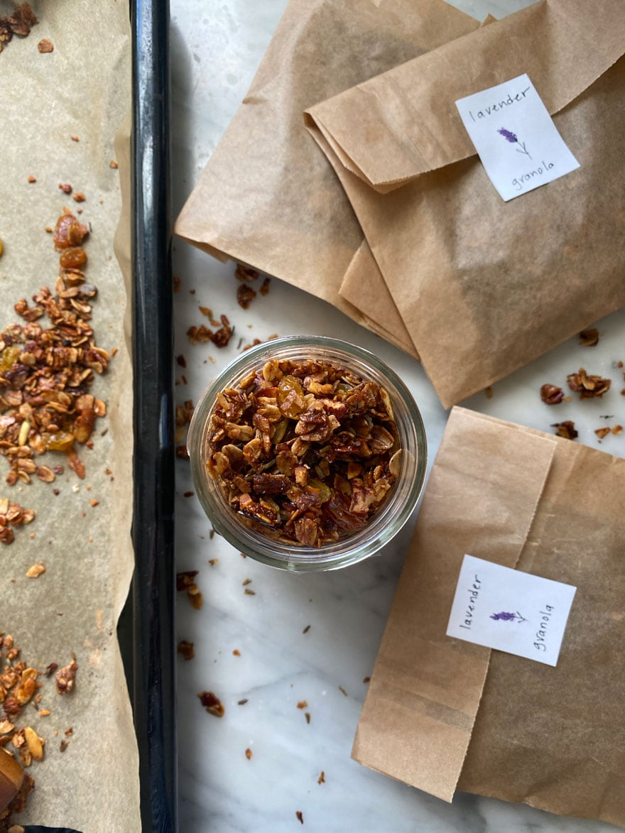 granola on pan with parchment paper and a jar with granola