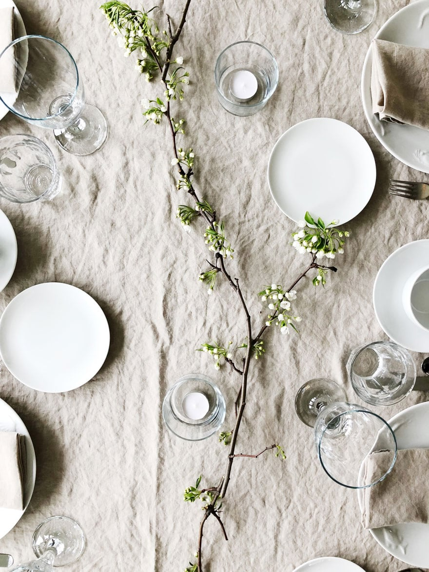 linen tablecloth with white dishes and cut branches laying on table