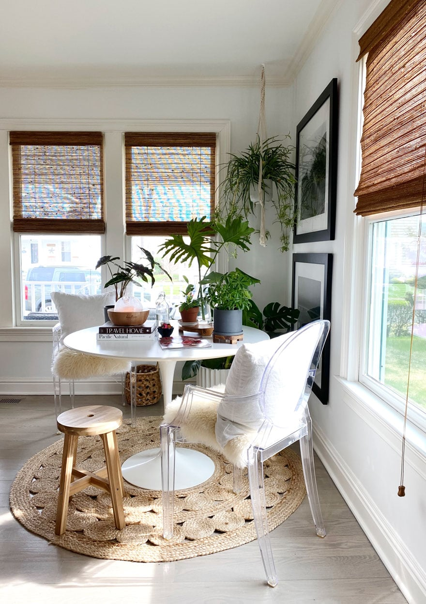 white Saarinen dining table in corner of room with plants
