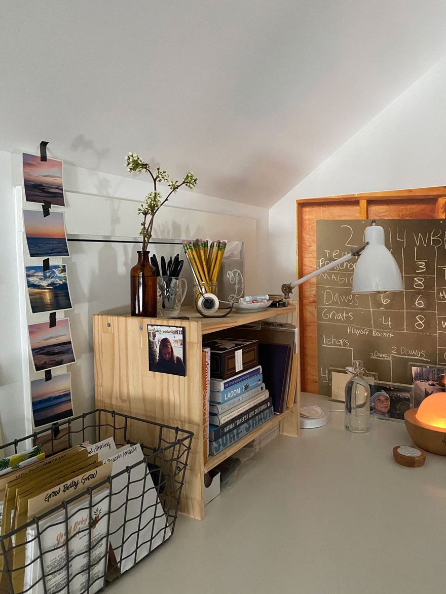 desk with photos, lamp, basket, bottle with flowers