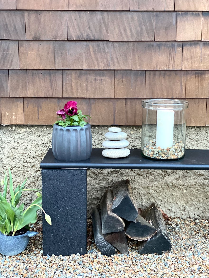black diy bench with stacjked rocks and small black planter with pansies