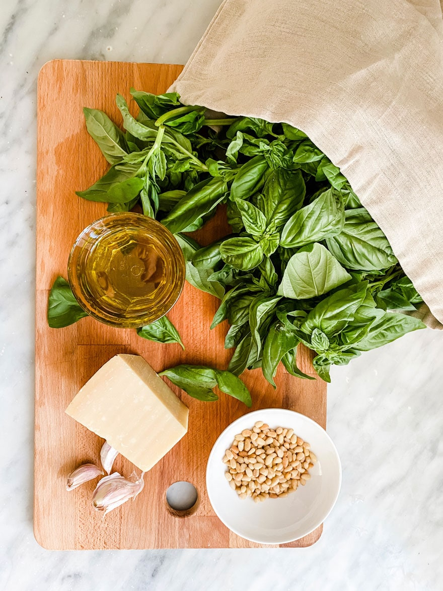 Ingredients for basil pesto on wood cutting board