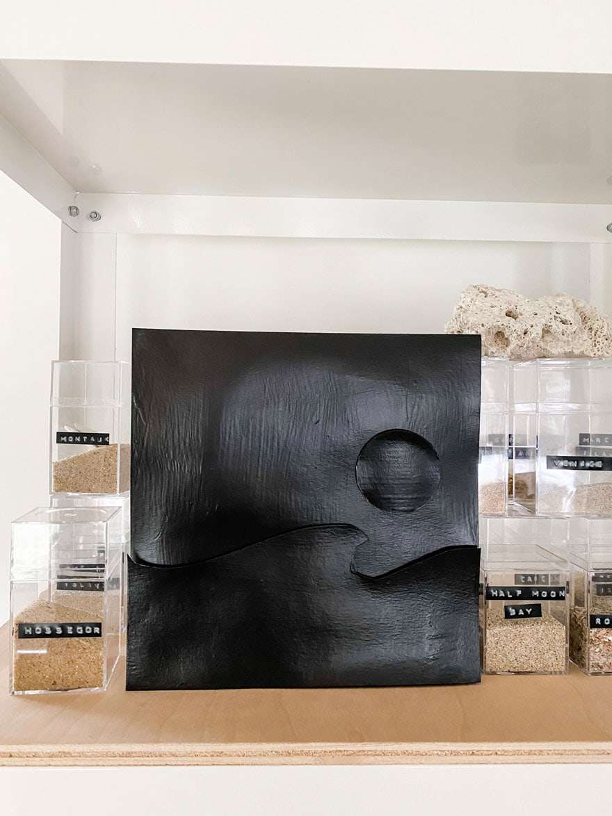 black painted collage with boxes of sand