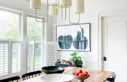 white dining room with farm table modern bowls and black chairs
