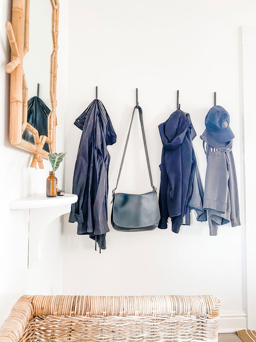 mirror, shelf, coats, bag on hooks on white walls