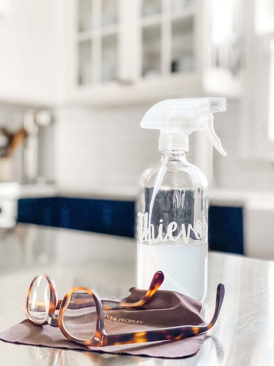 bottle of cleaner, eye glasses and brown cloth on counter