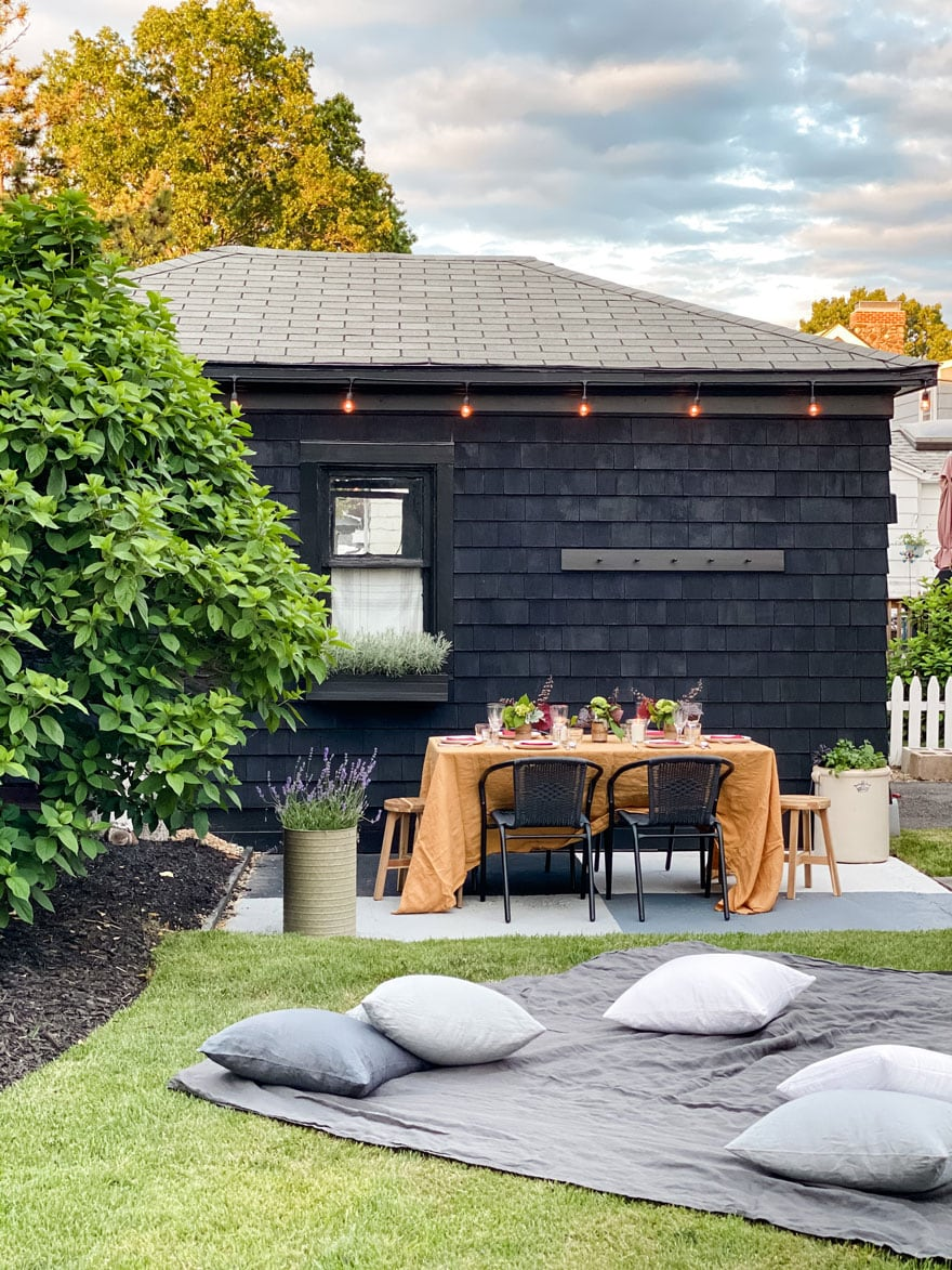 black garage with string lights and table set up with gold cloth, pillows in the yard