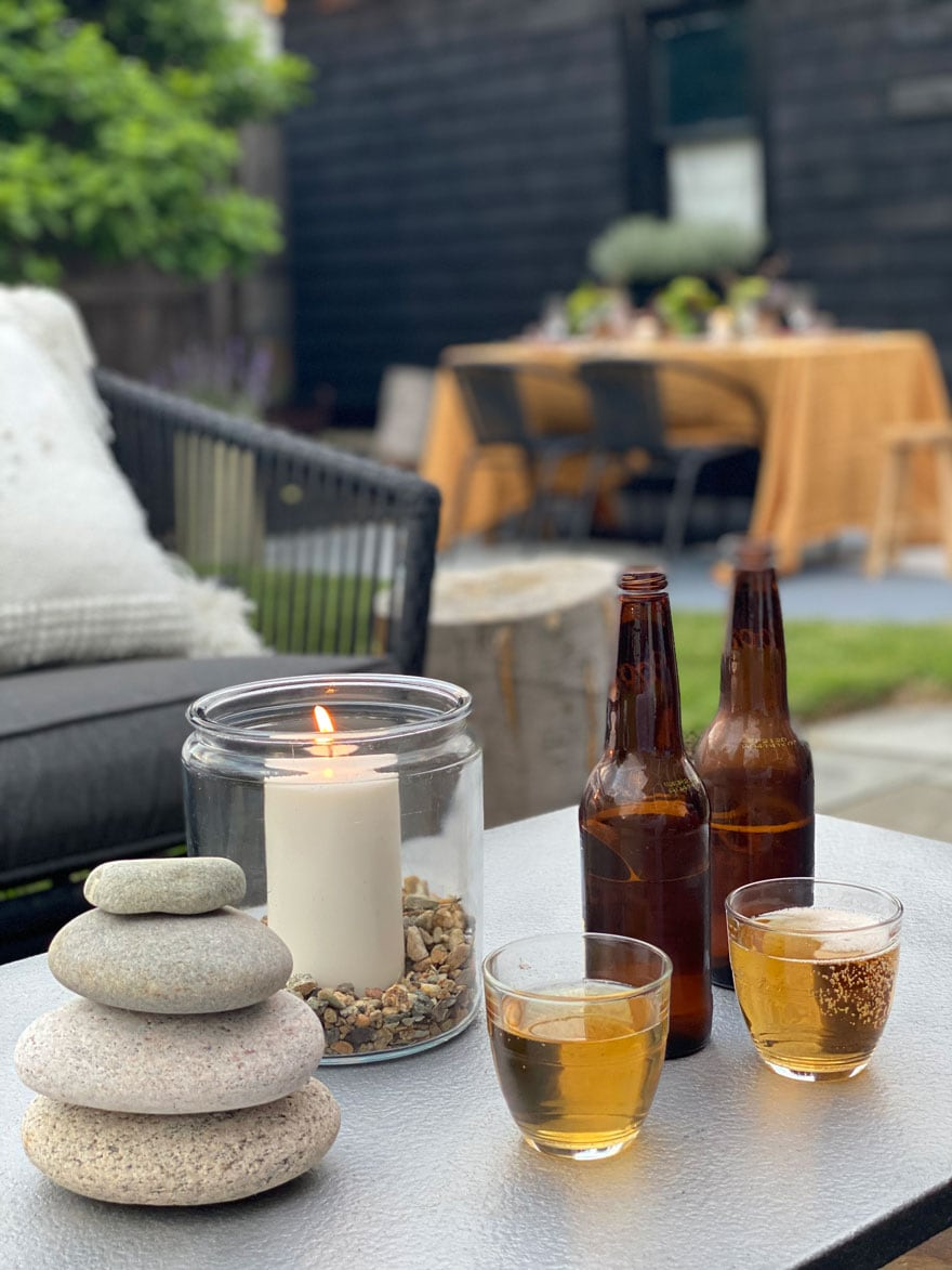 amber bottles beer glasses on table in backyard