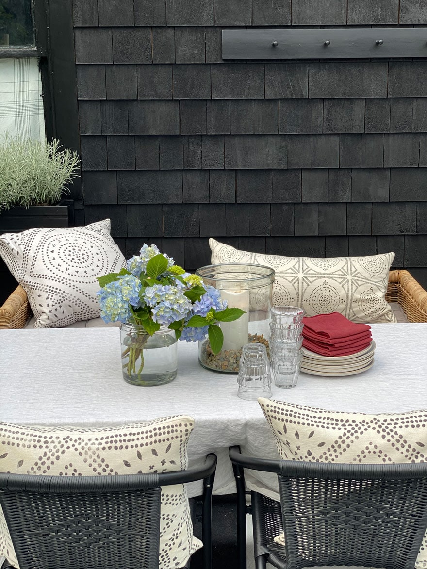 outdoor space with table, flowers, plates, napkins