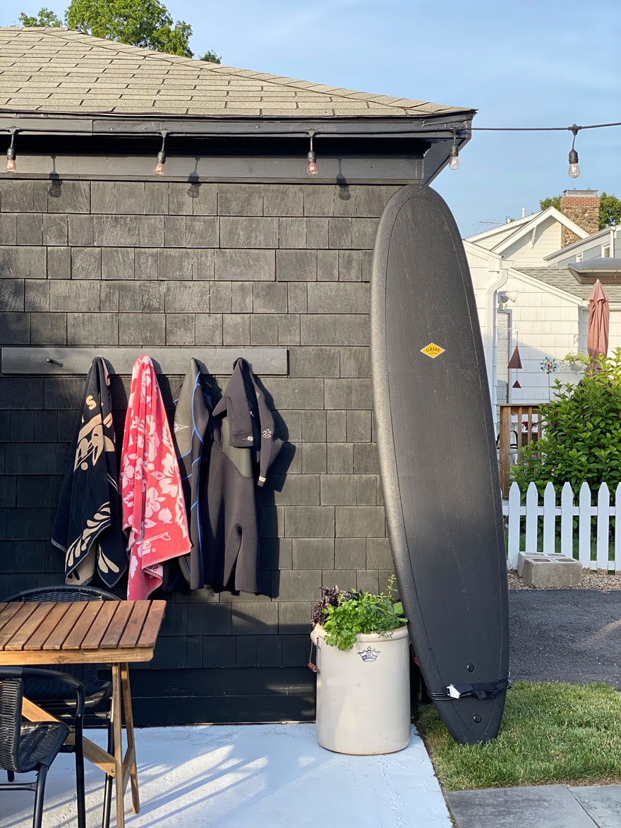 surf board against black house with hooks and towels