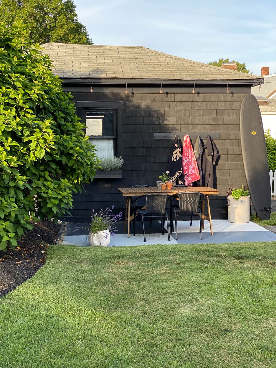 side of garage painted black with towels and wetsuits on hooks, table, chairs, planter