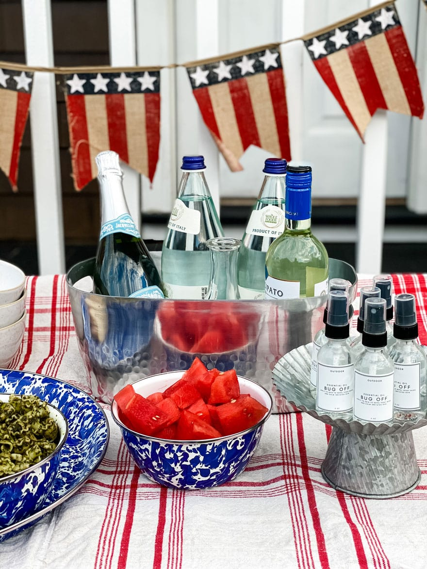 watermelon in blue and white bowl, flag banner on a potting bench with a tablecloth