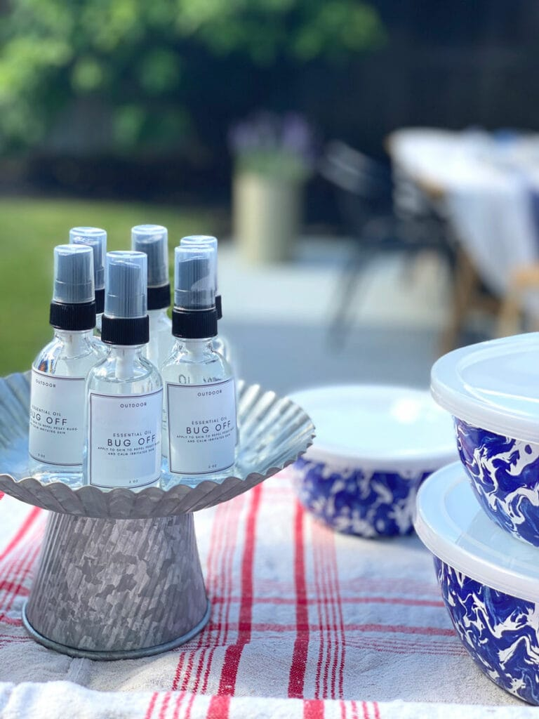 small clear bottles of bug off on galvanized cake stand