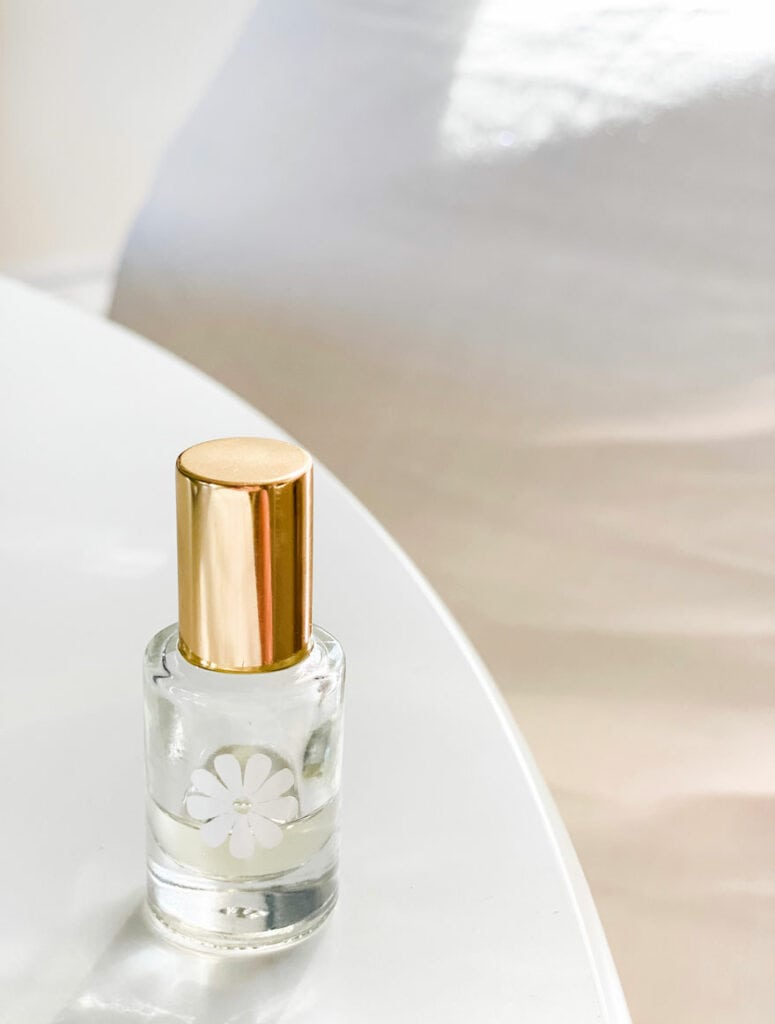 small perfume bottle with daisy