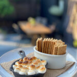 a small skillet with toasted marshmallows and a ramekin of graham crackers