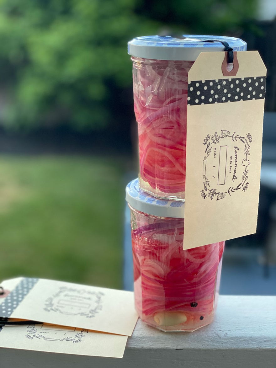 jars of pickled red onions on ledge with green faded out background
