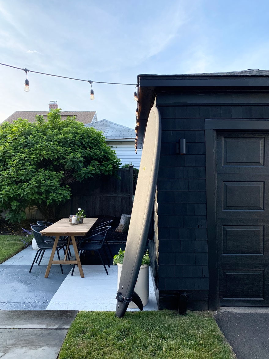 black surf board leaning against a black garage of a beach house