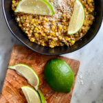 skillet with corn and limes on a wood cutting board