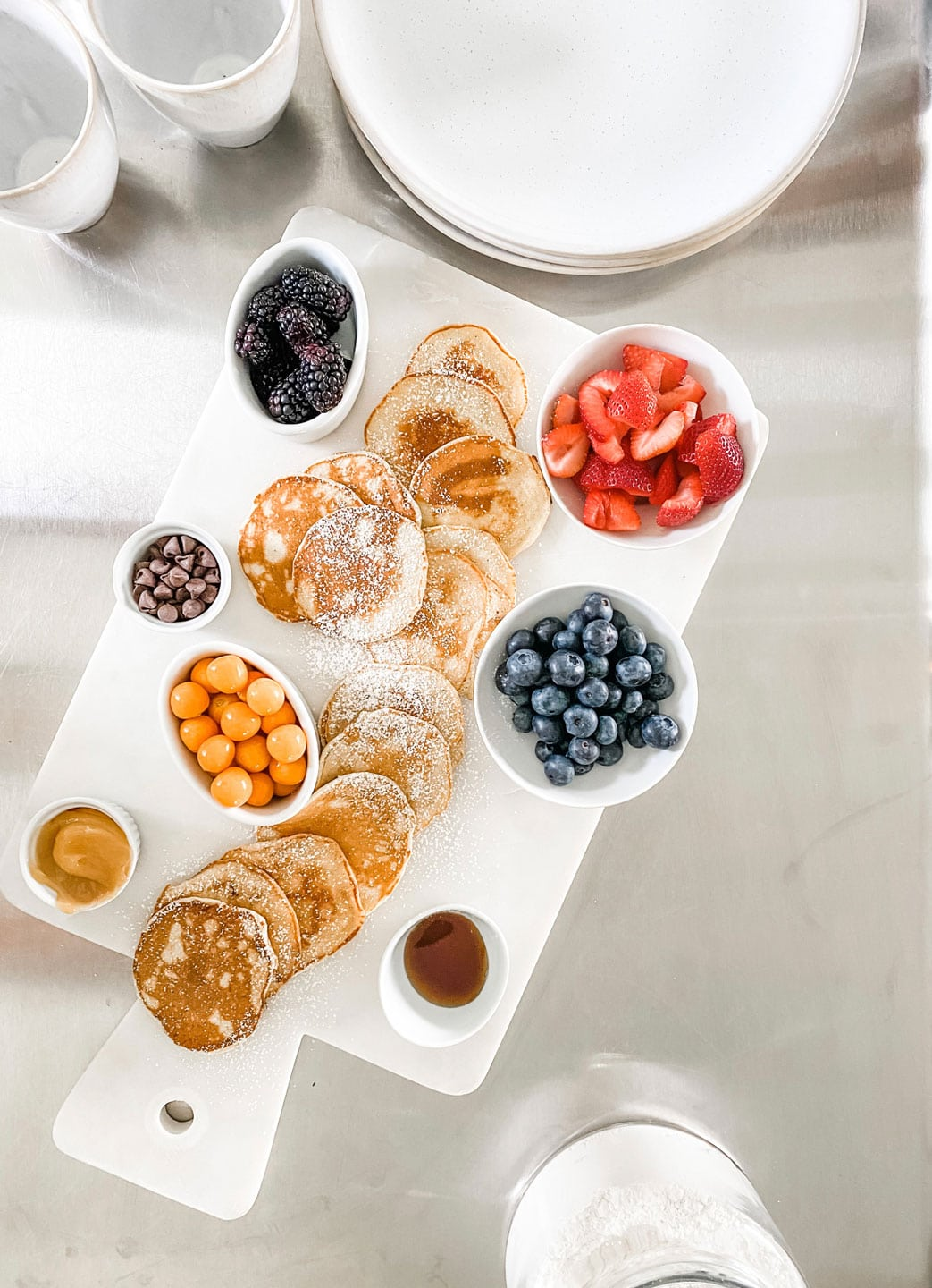a white marble brunch board with lemon ricotta pancakes and fruit