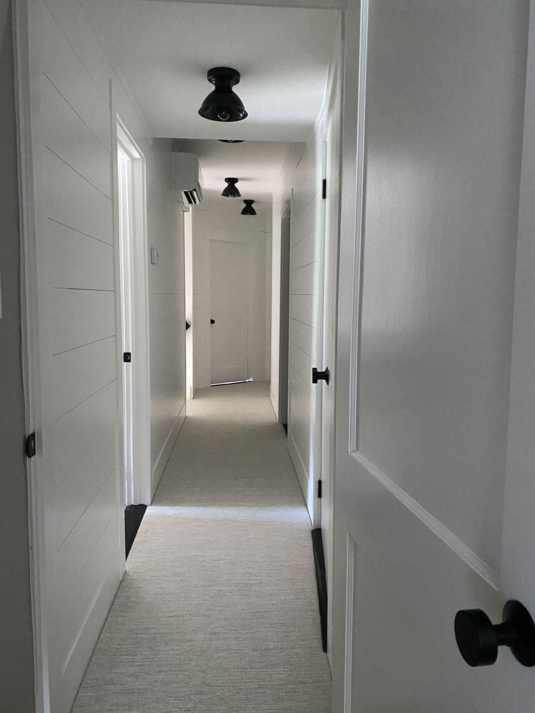 white hallway with black hardware and surface mount lights