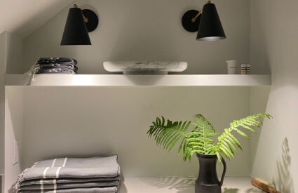 2 black sconces over white shelf, taels, fern in black pitcher, marble tray on shelf