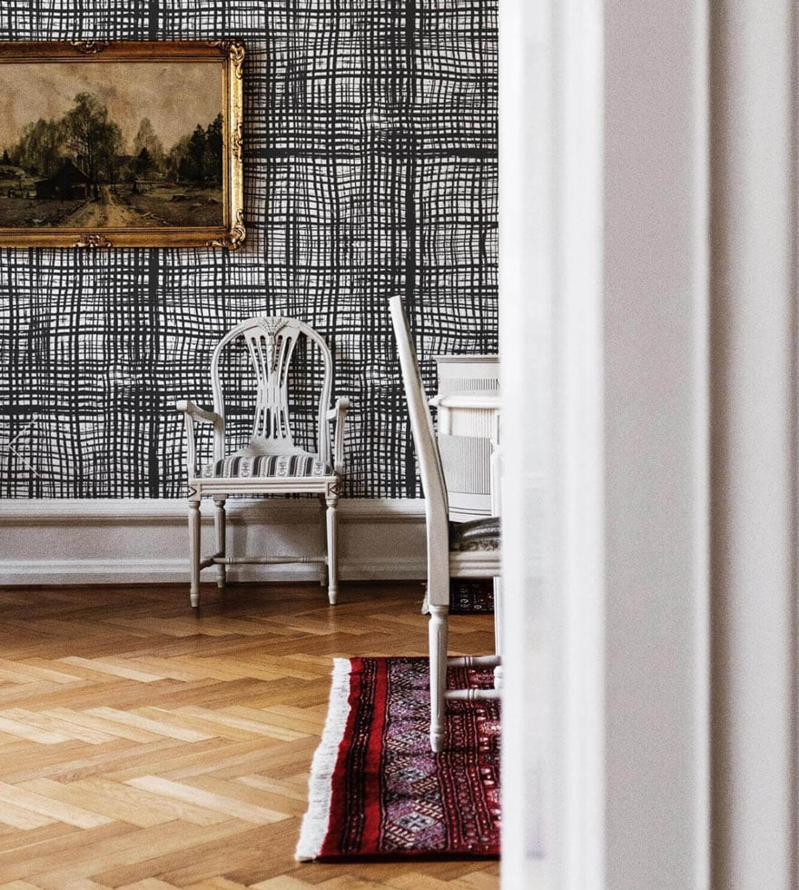 herringbone wood floors, black and white graphic wallpaper, old paintings, chair, rug
