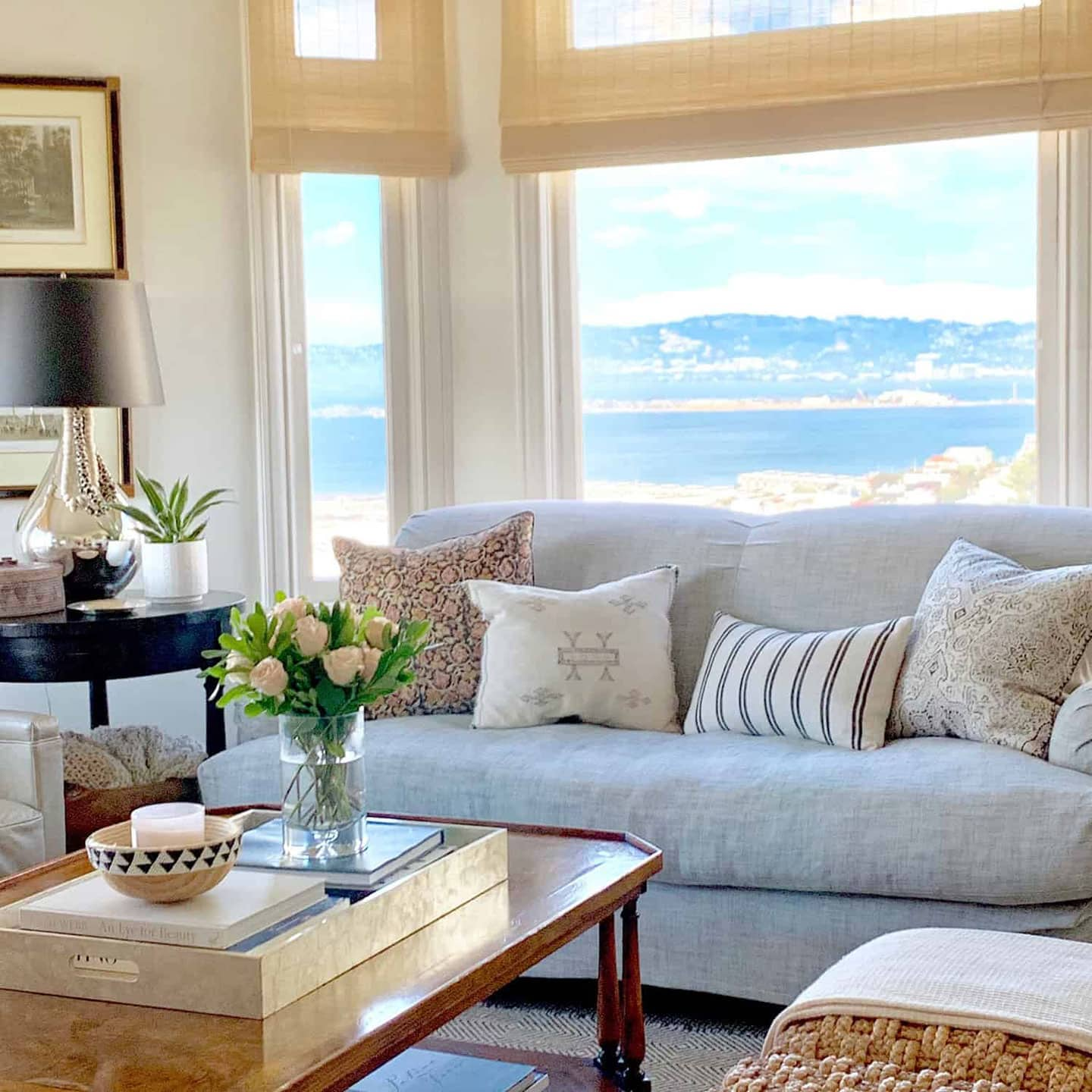 sofa with pillows. art, lamp, coffee table, large window with views