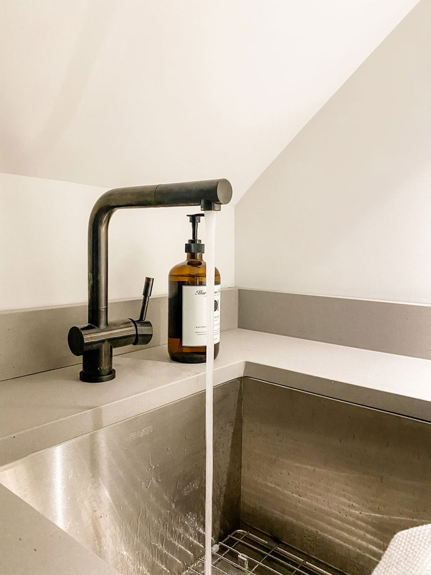 sink with simple black faucet with water running, amber bottle of soap