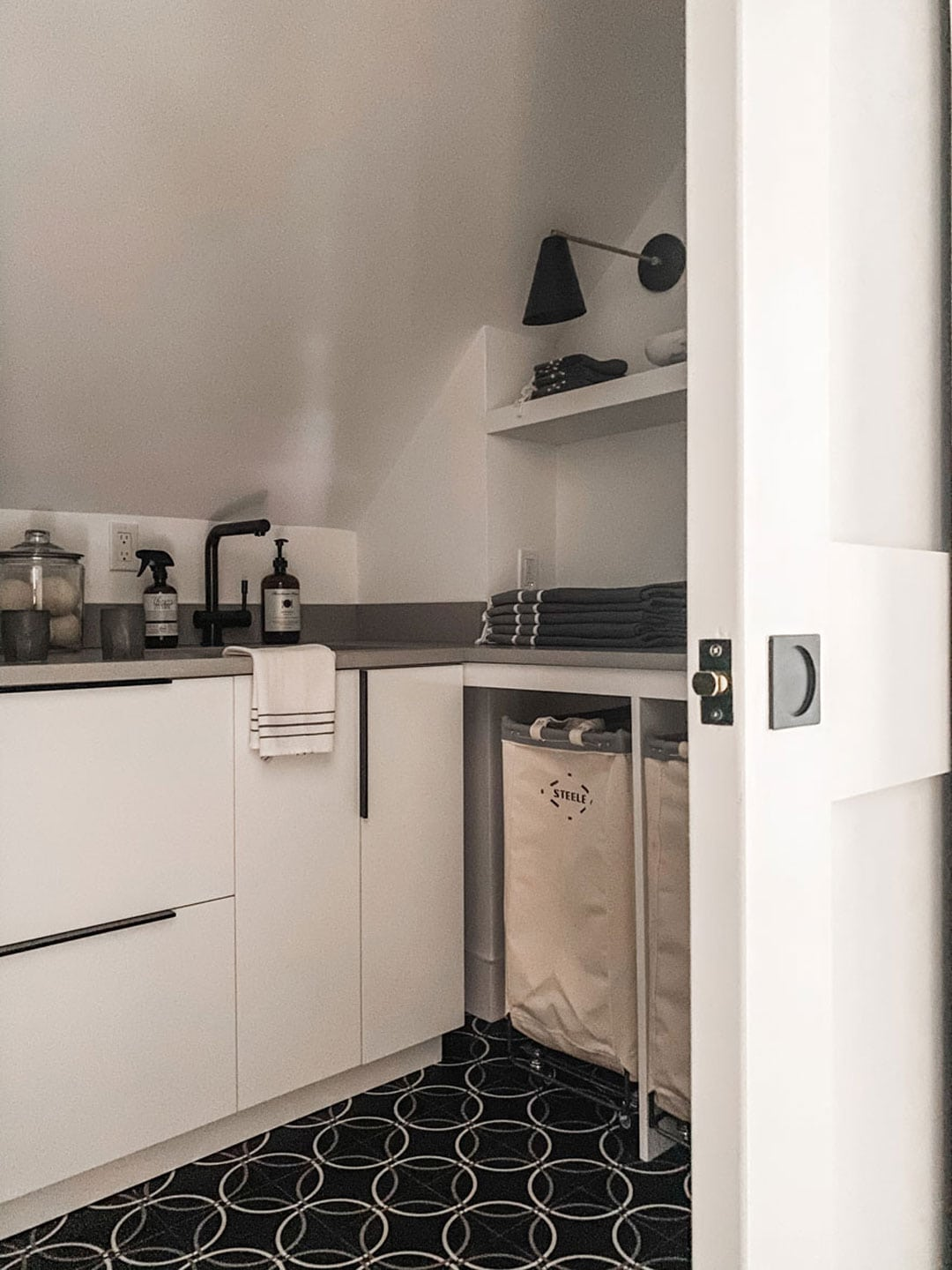 white cabinets, sink, laundry bins. sconce