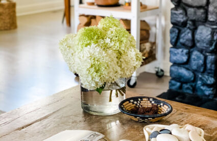 a coffee table with the Travel Home book open and fresh flowers