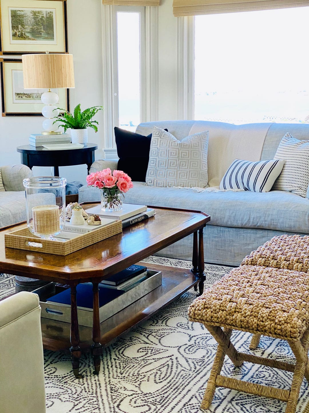 coffee table, stools, flowers, plant, sofa with pillows, lamp