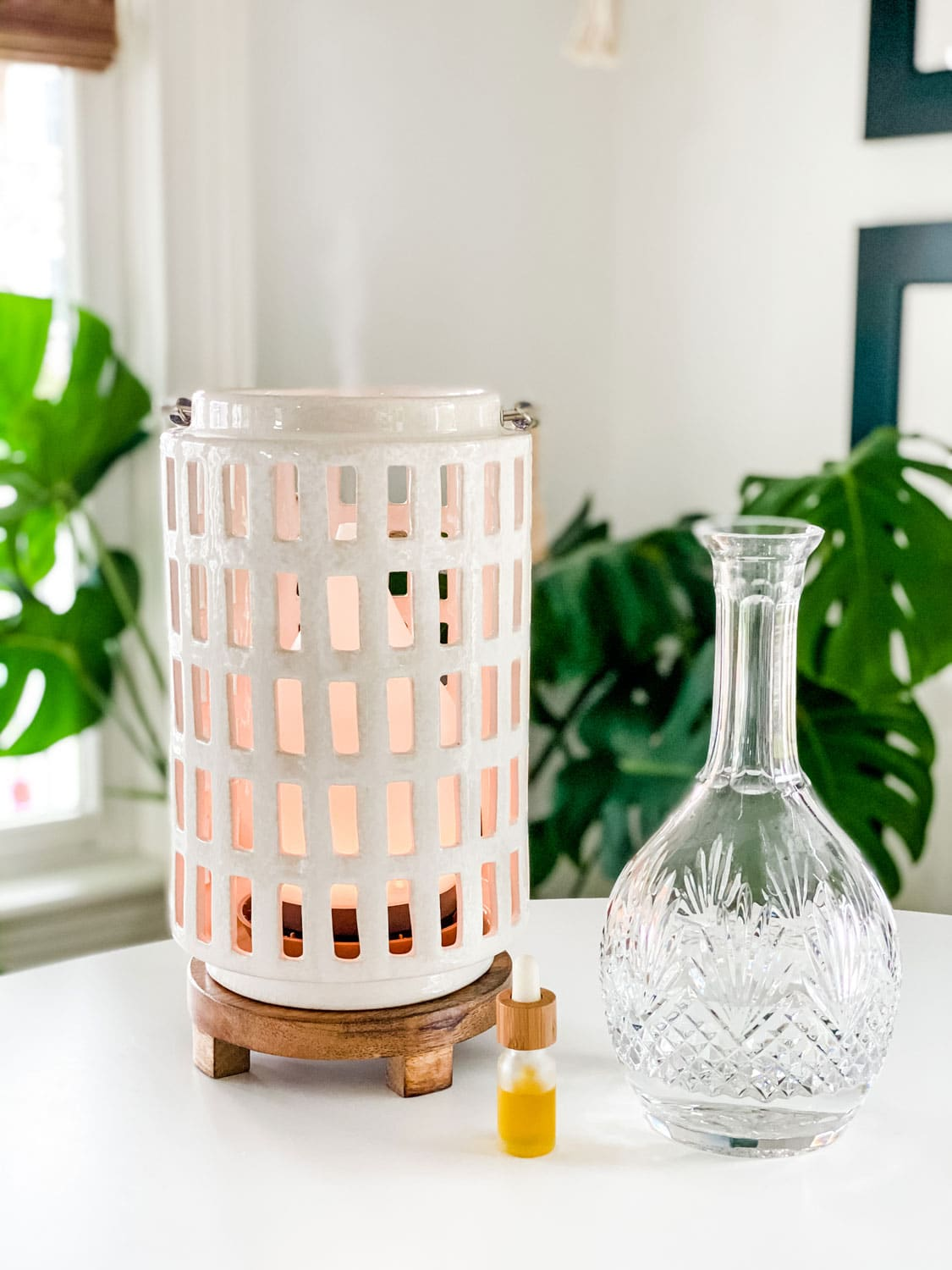 ceramic lantern on table with crystal glass bottle and plants