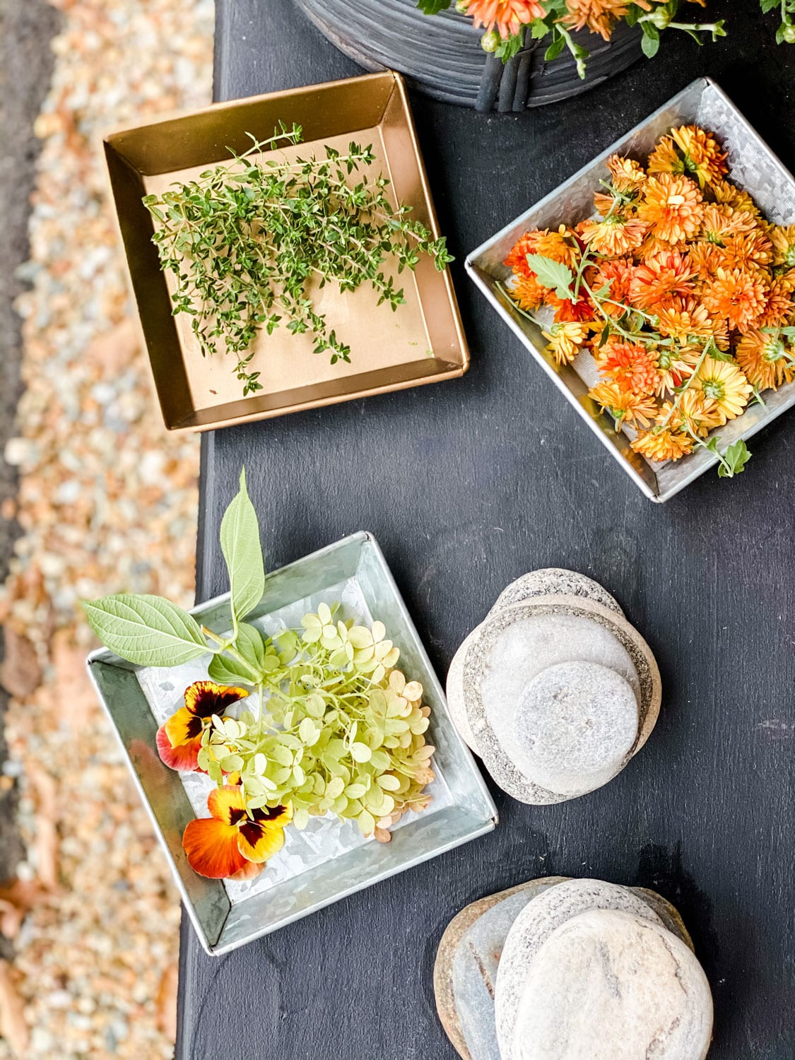 foraged flowers in trays on black bench with stacked rocks