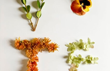 V-O-T-E in foraged flowers on white background