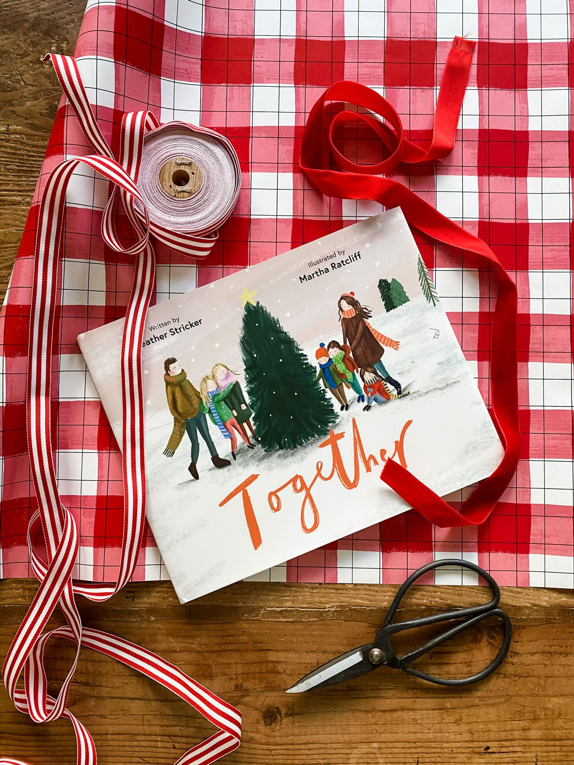 Together book on table with Christmas gift wrap and presents