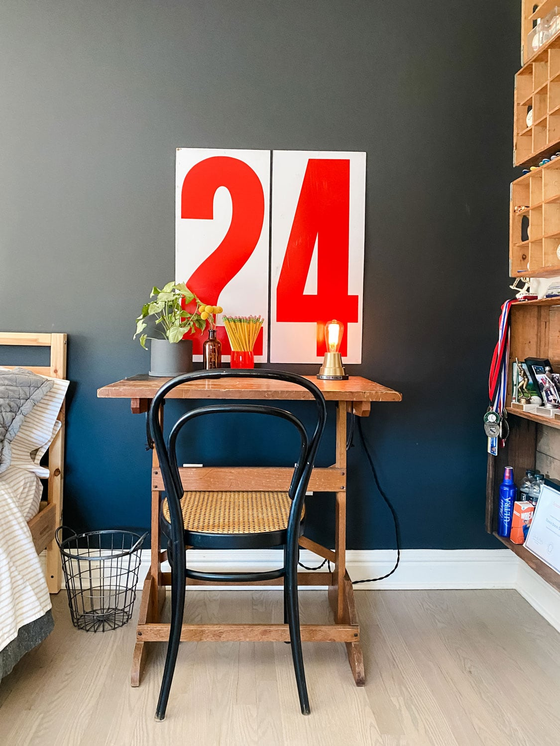old desk, chair, vintage gas station numbers on black wall