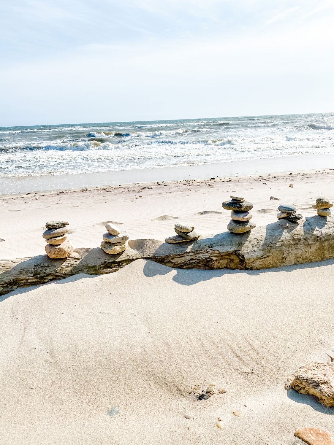 stacked rocks on driftwood at the beach