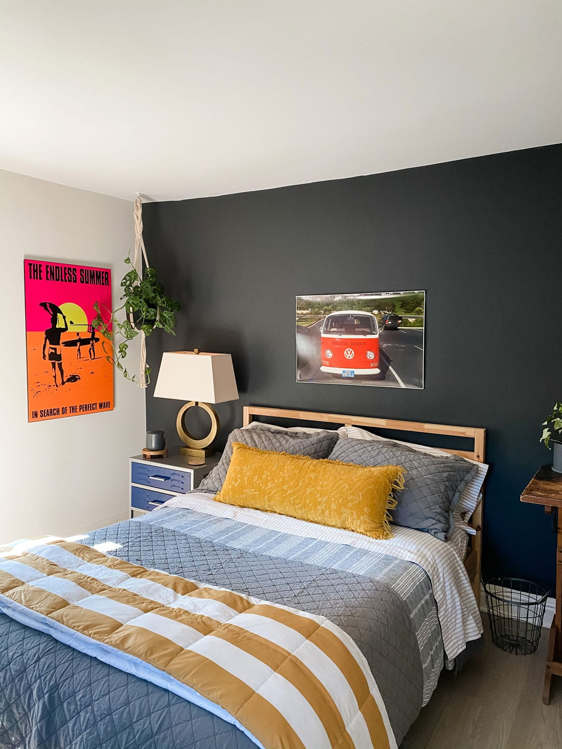 bedroom with black walls, bright colored poster, gray and gold bedding