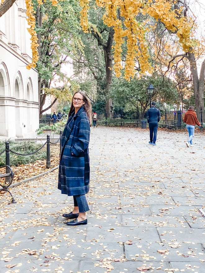 woman in plaid long coat under gingko tree in the fall in nyc