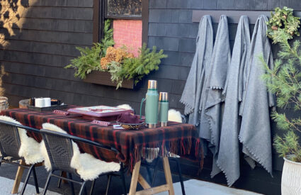 a table with a plaid throw, chairs, fire in a fire pit, black building with a window box