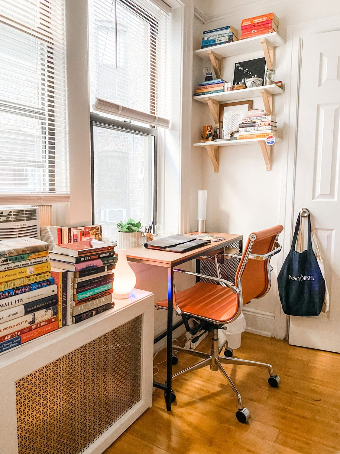 small desk with orange leather desk chair in a New York city apartment