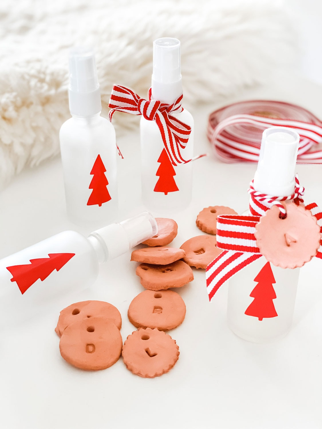 small frosted glass bottles with red tree decals and red and white ribbon with clay tag diffusers