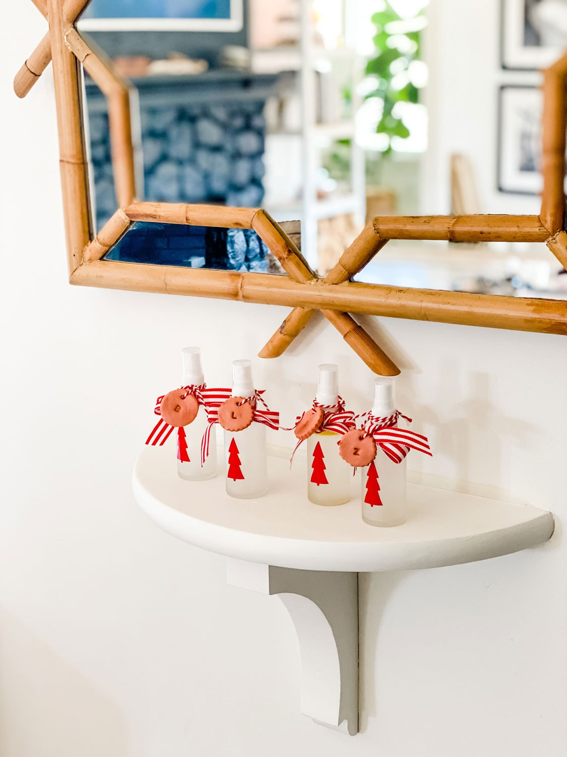 small frosted glass bottles with red tree decals and red and white ribbon with clay tag diffusers on small shelf under mirror