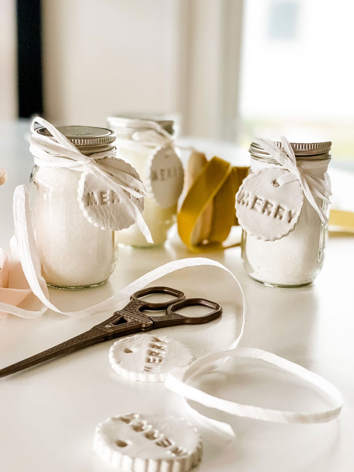 small jars with clay tags, ribbons, scissors
