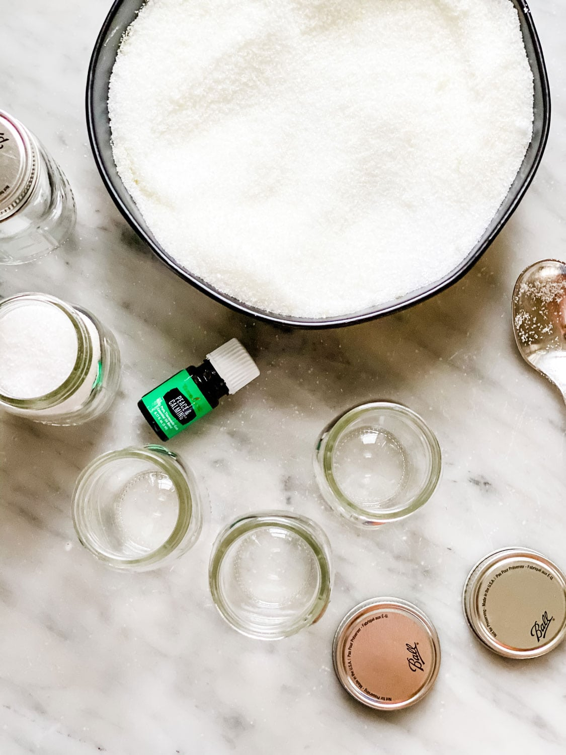 small glass jars, bowl with salt and bottle of essential oil