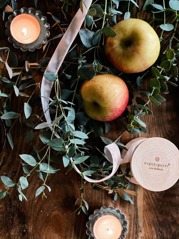 apples, eucalyptus and ribbon on farm table