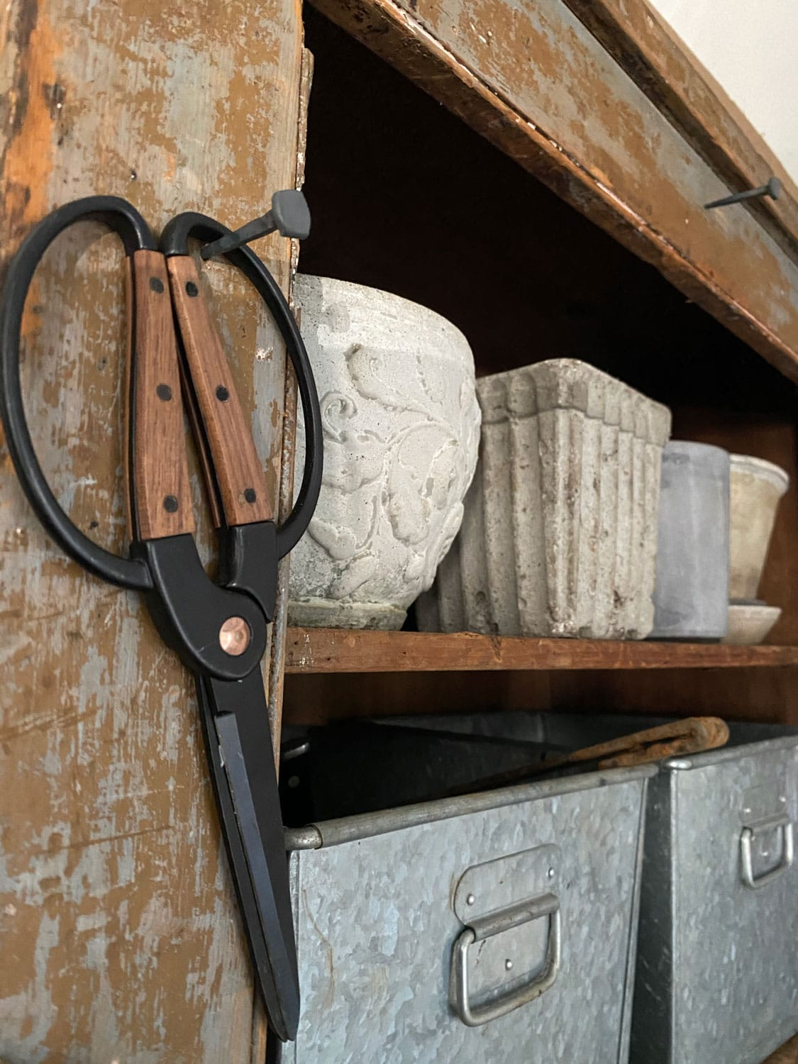 shelf or hutch with small cement planters and scissors on a rustic nail